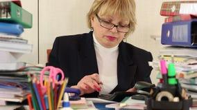 Guarda-livros da mulher entre papéis comerciais, com calculadora e a pena vermelha video estoque