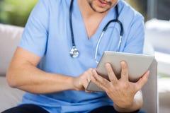 Guarda masculino que usa o tablet pc ao sentar-se Imagens de Stock