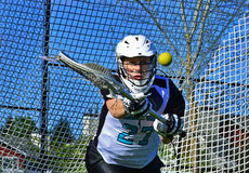 Guarda-redes das meninas da lacrosse que alcança para a bola Fotos de Stock Royalty Free