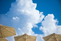 Guarda-sóis com opinião e nuvens de céu azul fotografia de stock