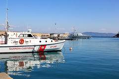 Guardacostas en el puerto de Oporto Santo Stefano, Italia Imágenes de archivo libres de regalías