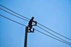 Guardalinee dell'elettricista che ripara lavoro sul palo di potere elettrico della posta Immagini Stock