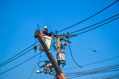 Guardalinee dell'elettricista che ripara lavoro sul palo di potere elettrico della posta Fotografia Stock