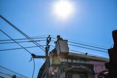 Guardalinee dell'elettricista che ripara lavoro sul palo di potere elettrico della posta Fotografie Stock