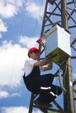 Guardalinee dell'elettricista di potenza sul lavoro sul palo Fotografia Stock