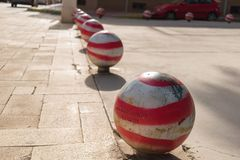Guardamar del Segura, Alicante, Spain; December 8 2.017: Red and white bollards on stone sidewalk. At sunset Stock Images