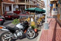 Guardamar del Segura, Spanje - Juni 26, 2016: Straat in Valencia Een straatkoffie en een motorfiets Royalty-vrije Stock Foto