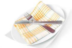 Guardanapo, dobrado em uma placa com faca e forquilha Imagens de Stock Royalty Free