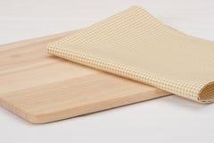 Guardanapo natural do algodão e placa de madeira no branco imagem de stock