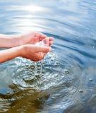 Guardando a água nas mãos colocadas Imagem de Stock Royalty Free