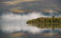 Guardando attraverso Loch Lomond verso Inchmurrin e un yacht immagini stock libere da diritti
