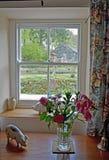 Guardando attraverso una finestra di vetro del cottage fuori nel giardino in cui potete vedere un vecchio granaio, uno stagno e l immagine stock libera da diritti