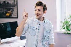 Guardando dagli uomini sorridenti nell'ufficio Progettista alla moda sul lavoro Il lavoratore ha ottenuto l'idea fotografie stock