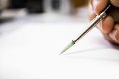 Guardando a escova da arte no Livro Branco Imagens de Stock Royalty Free