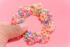 Guardando Fried Donuts no fundo cor-de-rosa imagem de stock