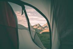 Guardando fuori la montagna abbellisca all'alba dall'interno della tenda di campeggio Avventuri il viaggio sulle alpi europee mae Fotografia Stock