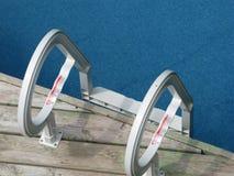 Guardando giù l'acqua blu della scala della piscina Immagine Stock