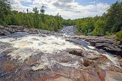 Guardando giù un fiume precipitante su Sunny Day Fotografia Stock