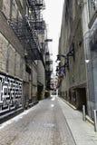 Guardando giù una strada del vicolo della città con i graffiti via d'annata dei lastricatori del mattone delle pareti sulla vecch Immagini Stock