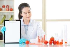 Guardando lavagna per appunti a registrare risultato dei test dell'alimento del gmo Fotografie Stock Libere da Diritti