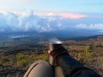 Guardando o copo do chá quente durante o tempo do nascer do sol nas montanhas imagens de stock