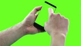 Guardando o dispositivo do écran sensível, o close-up da mão masculina usando um telefone esperto com chave do croma, esverdeia a video estoque