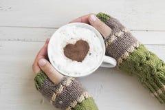 Guardando o Latte do café com os aquecedores acolhedores da mão de lãs fotografia de stock royalty free