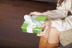 Guardando o presente verde no fundo do parquet Imagem de Stock
