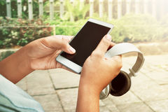 Guardando o smartphone e os fones de ouvido Fotos de Stock Royalty Free