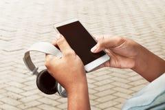 Guardando o smartphone e os fones de ouvido Foto de Stock Royalty Free