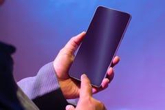 Guardando o smartphone no fundo de iluminação azulado fotos de stock