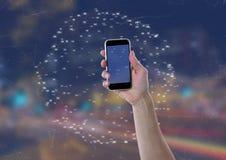Guardando o telefone celular contra a cidade da noite com conectores imagem de stock royalty free