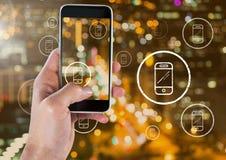 Guardando o telefone e os ícones do telefone sobre a cidade Fotografia de Stock Royalty Free