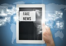 Guardando a tabuleta com notícia falsificada text e conecte fotografia de stock