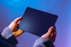 Guardando a tabuleta digital com ambas as mãos foto de stock