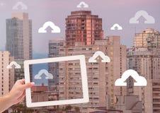 Guardando a tabuleta e os ícones da transferência de arquivo pela rede sobre a cidade Fotos de Stock Royalty Free