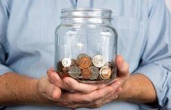 Guardando um frasco do dinheiro das moedas Foto de Stock