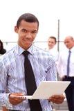 Guardando um tablet pc, um homem de negócios preto considerável novo é parte externa ereta de uma construção do negócio, segurame Imagens de Stock