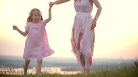 Guardar alegre da menina entrega sua dança da mamã no monte da grama no por do sol do verão filme