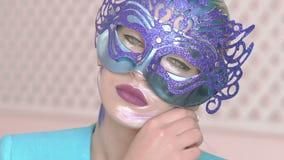 Guardare fisso degli occhi verdi della ragazza misteriosa nella maschera veneziana con trucco di arte di inverno video d archivio