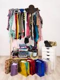Guardaroba con i vestiti ed i sacchetti della spesa Fotografie Stock