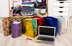 Guardaroba con i vestiti ed i sacchetti della spesa, sulla linea acquisto Fotografia Stock Libera da Diritti