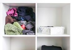 Guardaroba domestico con differenti vestiti Piccola organizzazione dello spazio Il contrasto di ordine e di disordine fotografia stock
