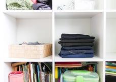Guardaroba domestico con differenti vestiti Piccola organizzazione dello spazio Il contrasto di ordine e di disordine fotografia stock libera da diritti