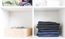 Guardaroba domestico con differenti vestiti Piccola organizzazione dello spazio Il contrasto di ordine e di disordine immagini stock libere da diritti