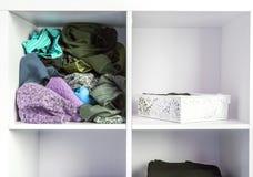 Guardaroba domestico con differenti vestiti Piccola organizzazione dello spazio Il contrasto di ordine e di disordine immagini stock