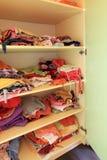 Guardarropa con ropa del niño en estantes Imagen de archivo libre de regalías