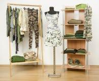Guardarropa con ropa y accesorios del modelo del camo Imagenes de archivo