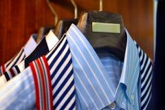 Guardarropa con texturas rayadas y llanas clásicas de las camisas, el gabinete almacenado, negocio de la ropa de la ropa Fotografía de archivo