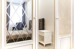 Guardarropa en el dormitorio con un espejo liso y con un cartabón Interior fotografía de archivo